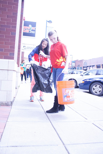 Athena Sargent (front) and Selena Wang, eighth grader at Anthony Middle School, volunteer at Clean Up MHK in Aggieville on Sunday, April 22, 2018. (Tiffany Roney | Collegian Media Group)