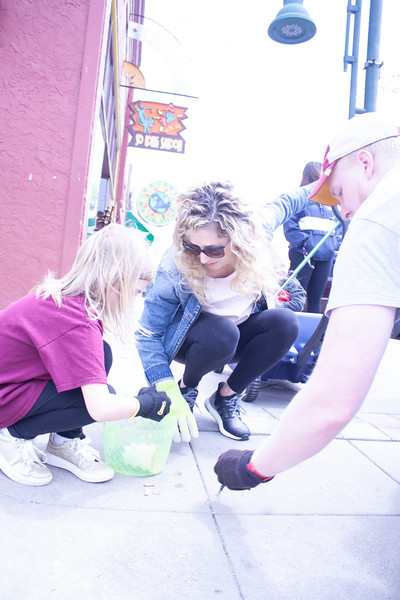 Halley Hartenbower, program manager for the National Bio and Agro-defense Facility, and her daughter Maebel pick up litter in Aggieville with other volunteers as part of Clean Up MHK on Sunday, April 22, 2018. (Tiffany Roney | Collegian Media Group)