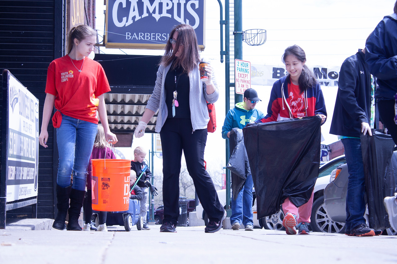 Athena Sargent (from left), eighth grader at Anthony Middle School; Paula Dover, coordinator of Youth Volunteer Corps; and Selena Wang, eighth grader at Anthony Middle School, volunteer at Clean Up MHK in Aggieville on Sunday, April 22, 2018. (Tiffany Roney | Collegian Media Group)