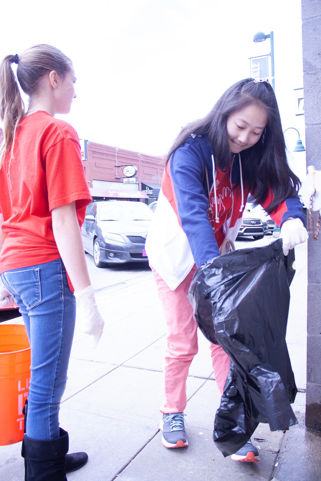 Selena Wang (right) and Athena Sargent, eighth graders at Anthony Middle School, volunteer at Clean Up MHK in Aggieville on Sunday, April 22, 2018. (Tiffany Roney | Collegian Media Group)
