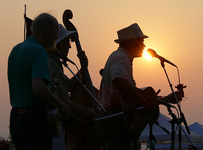 Pete Seeger, Mark Murphy and Guy Davis playing the closing ceremony of the 2006 Clearwater Great Hudson River Revival on the banks of the Huson River with the sun setting behind them.