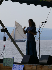 A sign language interpreter on the Hudson River stage as the SLoop Clearwater sails by.