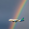 Airplane soaring by rainbow