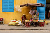 Woman  at market stand in front of yellow wall, Hoi An, Vietnam
