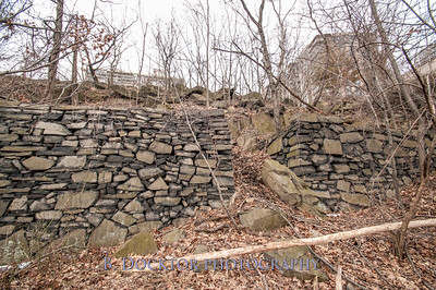 Two leveled areas with rock walls on three sides.
