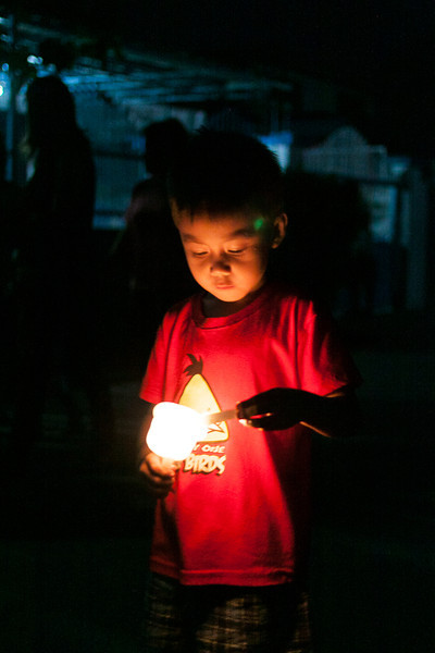 Boy lights candle for Feast of the Black Nazarene prayer procession