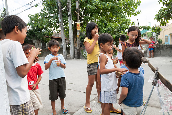 "Kids eating ""Taho"", soft tofu with caramelized syrup and tapioca balls"