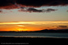 The sun goes down behind Greencastle, Donegal. Viewed from Gortmore, County Londonderry.