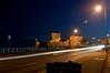 Speeding traffic passes Carrickfergus Castle at night