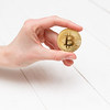 Woman's hand holds a gold coin bitcoin coin.