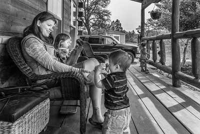 A mom sitting in a wicker chair spends time with two of her children on the front porch of their home while enjoying a cup of coffee.