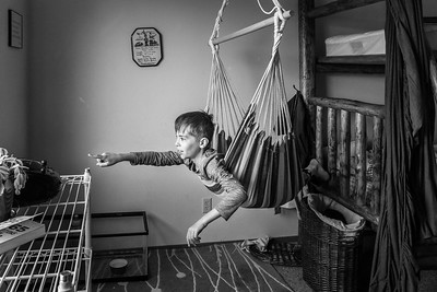 A boy in a hammock in his bedroom pointing out the window.