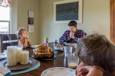 A father and his young daughter pray before the family has a pancake breakfast in their home at the dining room table.