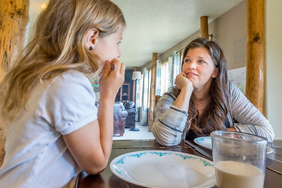 A mother and daughter having a talk over breakfast in their home.