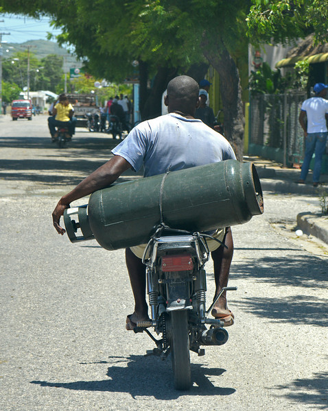 Dominicans use motorbikes as small trucks. Propane tanks are often carried in this style to the nearest station to be refilled, and I saw at least one rider with a washing machine strapped to his back.