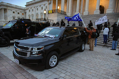 A federal vehicle sits with slashed tires in front of the U.S. Capitol building