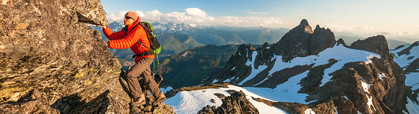 A climber scrambles up a rocky mountain ridge.