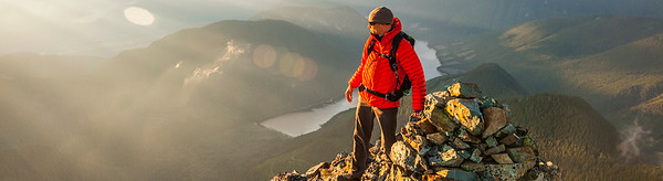 A climber stands on the summit of a rocky mountain.