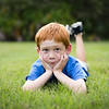 Little boy with red hair lying in the grass