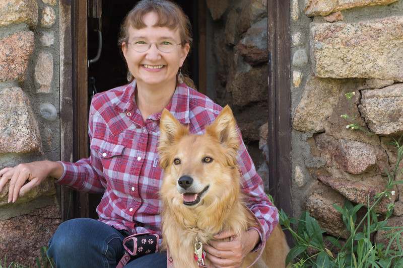 Portrait of a smiling woman in a red plaid shirt kneeling next to her dog, a golden smooth collie mix.