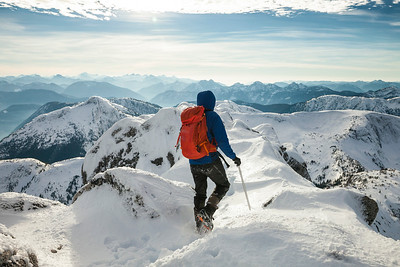 A mountaineer carefully walks across the summit ridge of Needle Peak.