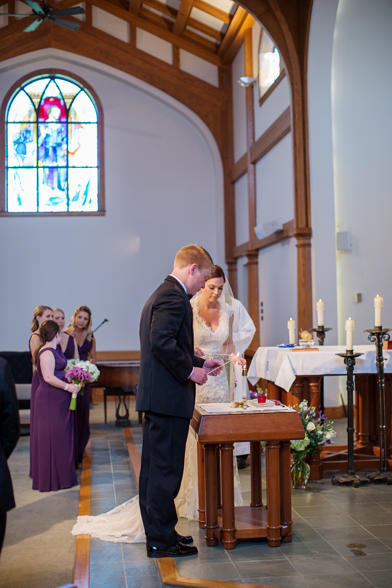 Photo of bride and groom light the unity candle at Loyola Blakefield High School Chapel wedding. Photos by Jalapeno Photography.