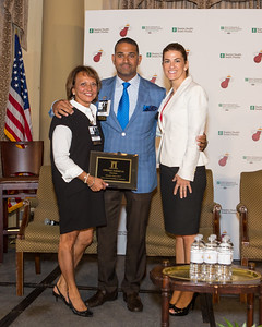 VP of International Development, Carolina Rendeiro, accepting the Trustee plaque from the Coral Gables Chamber.