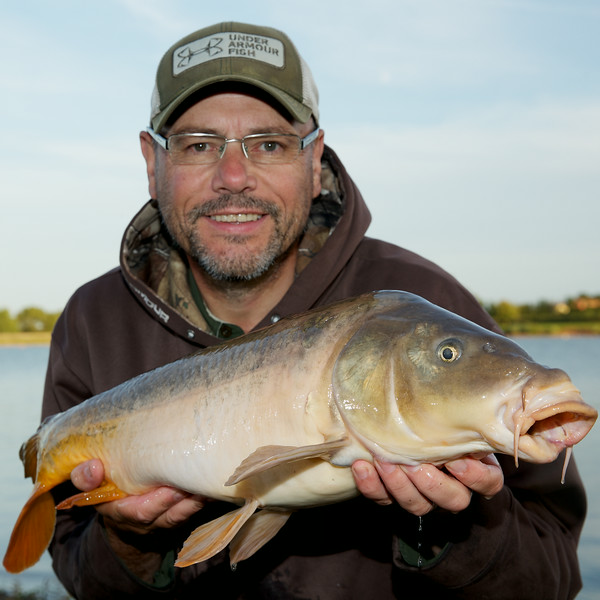 Brian Gay with an 11 lb mirror carp, it looks like a leather but there are a few scales at the base of the dorsal fin. © 2014 Shawn Kittridge / v2v-visuals.co.uk