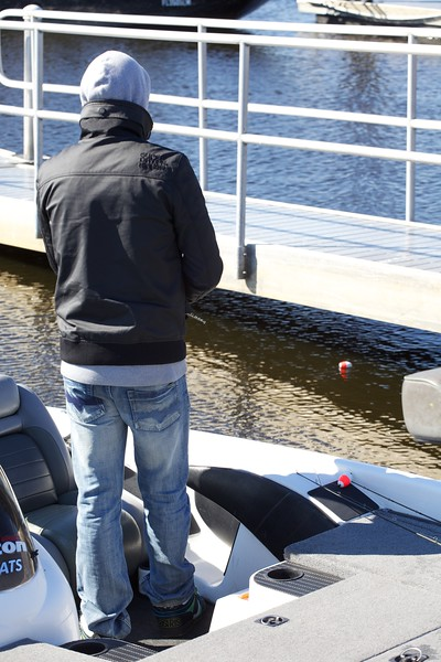 Professional bass guide Steve Boyd (wearing cap) and Oliver Gay fishing with a float under a dock walkway.