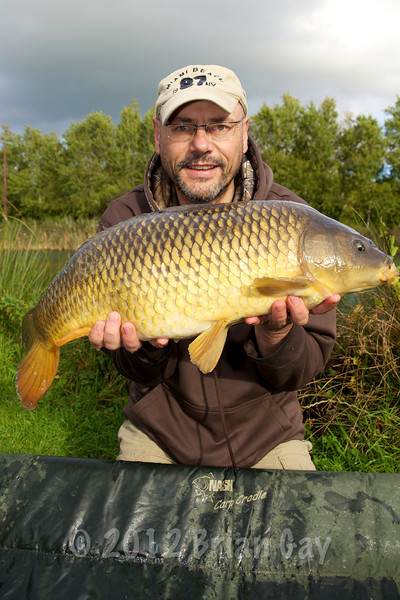 Brian Gay holds the 14 lb 8 oz common carp caught on dead maggots tipped with two buoyant fake maggots. © 2012 Brian Gay