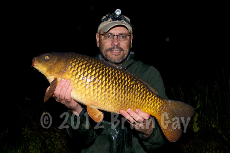Brian Gay with a 13 lb common carp caught on a maggot clip rig from the hot spot just as the light was fading. © 2012 Brian Gay