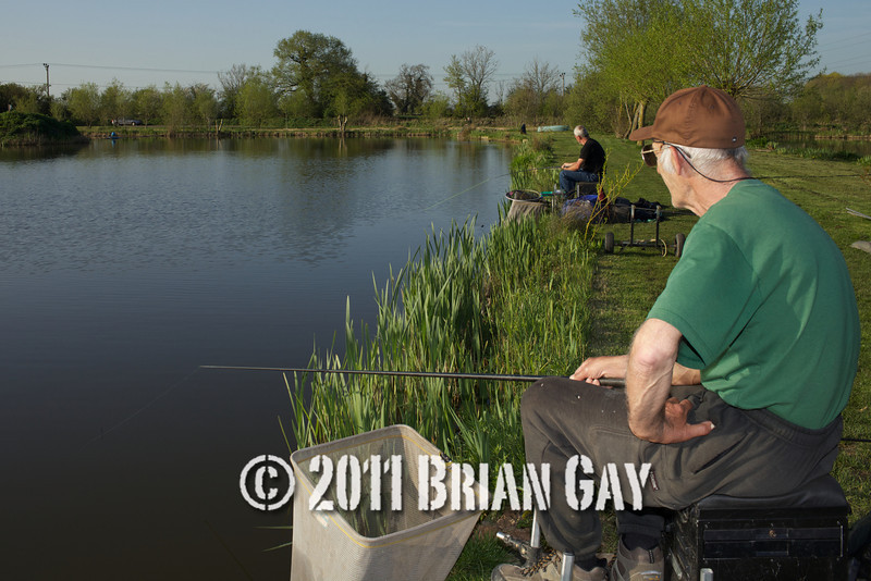 Jamie Cook plays a fish while Brian Gatiss looks on during their top kit challenge at the Tile pond, Sedges, Bridgwater, Somerset. © 2011 Brian Gay
