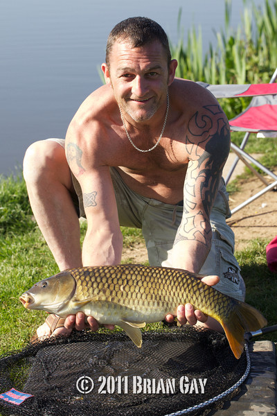 Travis Robinson with a common carp caught on floating bread from the Tile pond at The Sedges, Bridgwater, Somerset. © 2011 Brian Gay