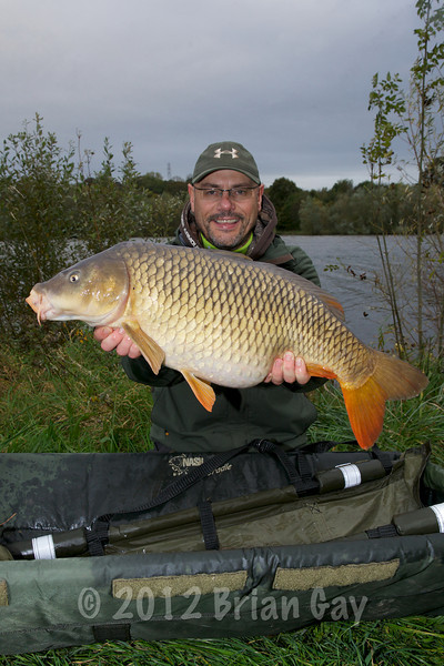 Brian Gay holds an 18 lb 12 oz common that fell to solid bag tactics at 80 yards with a 14 mm Mainline Cell boilie tipped with pink buoyant Drennan corn. Helicopter rig, 3 oz pear lead Fox bag trace size 8 hook. Sutton Bingham reservoir.