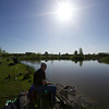 The sun shones brightly in a clear blue sky over Tile lake at The Sedges, Bridgwater, Somerset. Angler Jamie Cook nearest the camera.