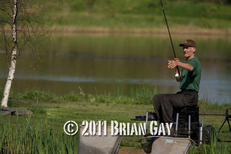 Brian Gatiss swings in a small skimmer on the causeway bank of the Tile pond at the Sedges, Bridgwater, Somerset. © 2011 Brian Gay