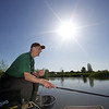 The sun shines brightly in a deep blue cloudless sky as Brian Gatiss fishing a top kit in the margins on the causeway bank of the Tile pond at the Sedges, Bridgwater, Somerset. © 2011 Brian Gay