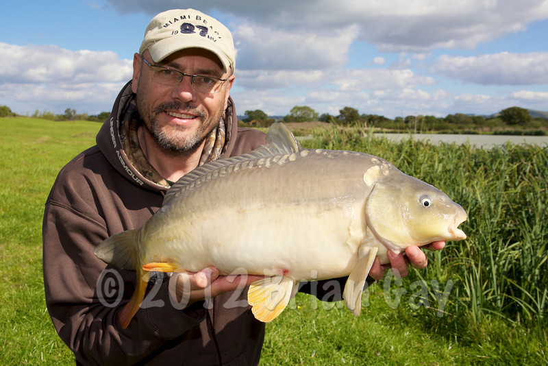 Brian Gay displays a 13 lb mirror carp that fell to the double fake corn set-up one pink and one yellow. Todber manor, Little Hayes. © 2011 Brian Gay