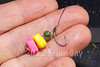 Close-up of two pieces of fake corn. One pink and one yellow from the Drennan buoyant plastic range. They are mounted on the hair of a barbelss Korda pretied KD rig. An Anchor camo shot balances the bait. © 2012 Brian Gay