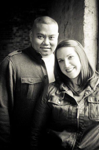 Couple in the window light at the Prairie St. Brewhouse, in Rockford, Il during an engagement portrait photo session.
