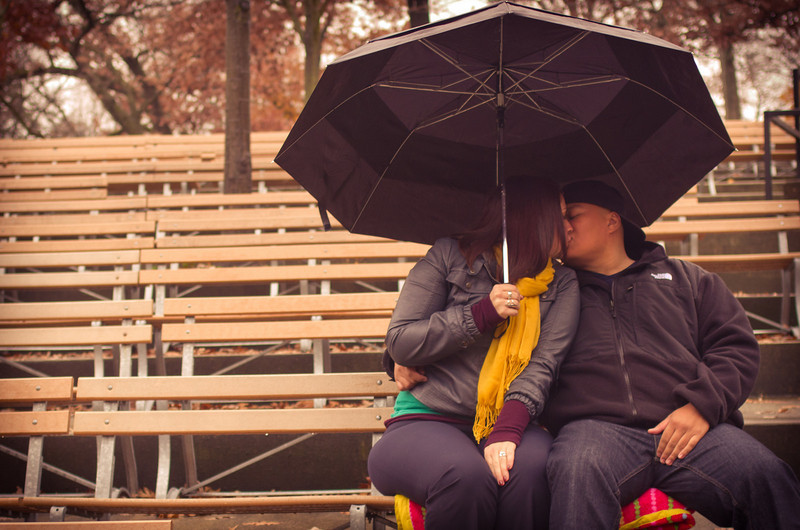 Couple share a romatic moment in the rain  during their autumn engagement portrait photo session at Sinnissippi Park in Rockford, IL.