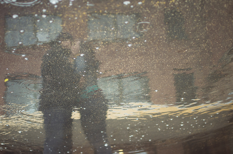 Romantic moment reflected in a puddle portrait outside the  Prairie St. Brewhouse, in downtown Rockford, IL, during an engagement portrait photo session.