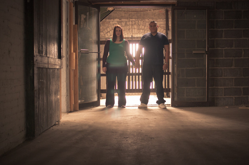 Couple share some moments by a vintage industrial elevator at the Prairie St. Brewhouse, in downtown Rockford, IL, during an engagement portrait photo session.
