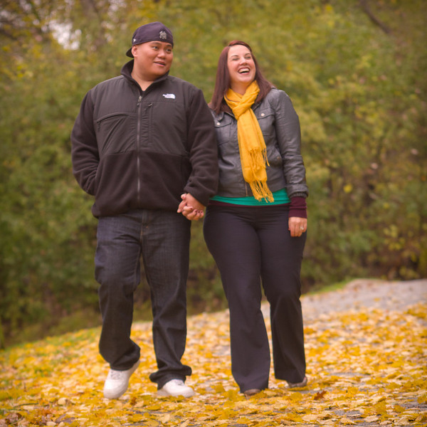 candid photo of a couple enjoying the fall colors during their autumn engagement portrait photo session at Sinnissippi Park in Rockford, IL.