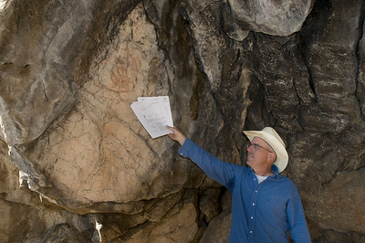 U.S. Forest Service Archaeologist Walt Allen points to a pictograph depicting a bear paw painted by the Salish people.