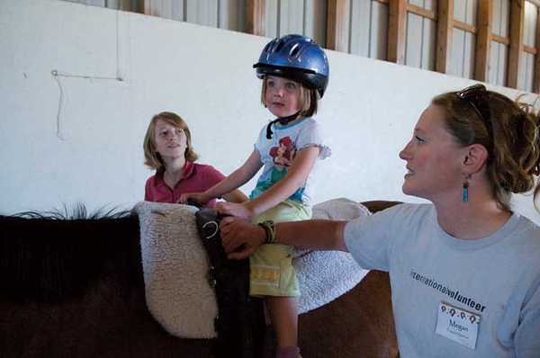Eagle Mount volunteers providing therapeutic recreation for children with disabilities in their equine facility.