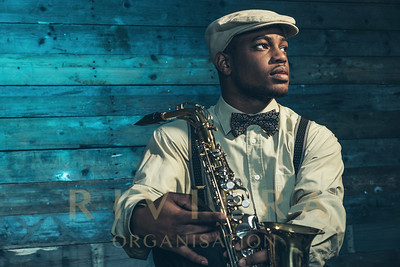 African american jazz musician with saxophone in front of old wooden wall.