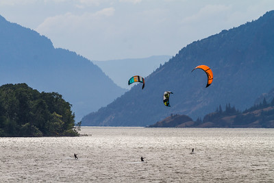 People paragliding over river - USA