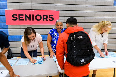 Instructional assistant Samia Kobzeff (blue shirt) hands out schedule to senior students. Back to school day at McNary High School on Wednesday, September 4, 2019 in Keizer, Ore.