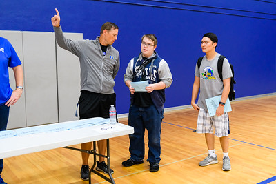 PE/weights teacher TJ Tomlin, left, gives schedules to junior students. Back to school day at McNary High School on Wednesday, September 4, 2019 in Keizer, Ore.